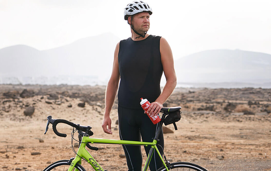 Man standing with his bike near a road with a desert in the background.