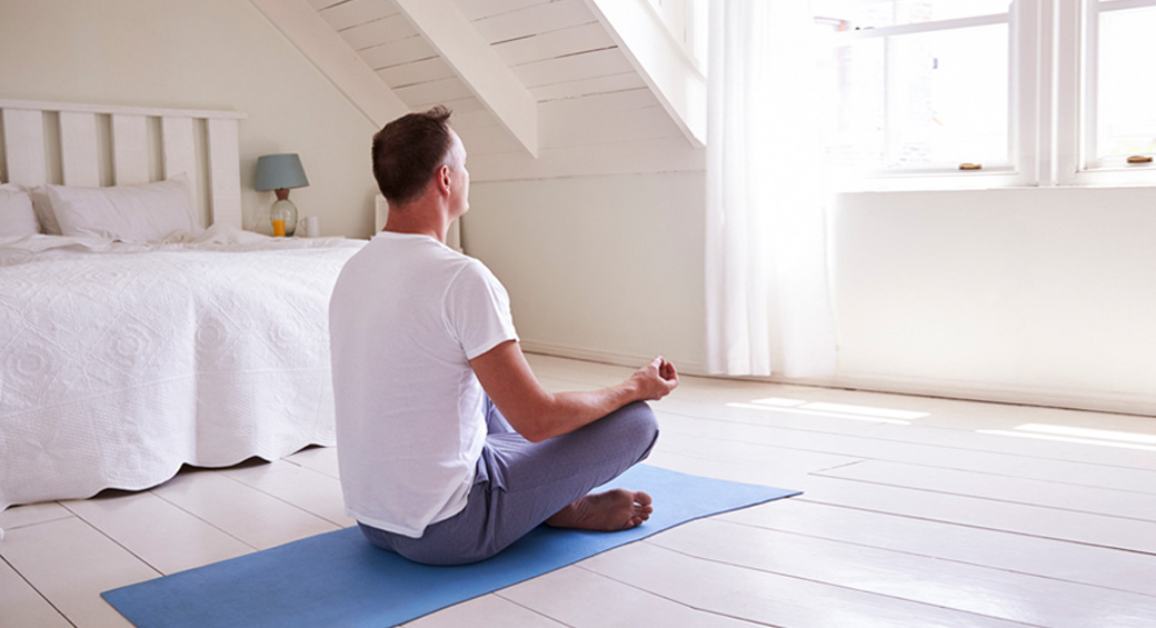 A light room with a man sitting on a blue mat doing yoga.